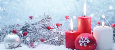 Christmas decoration with candles,fir branch and balls on snow.